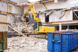 Hydraulic excavator working at the demolition of an old industrial building.